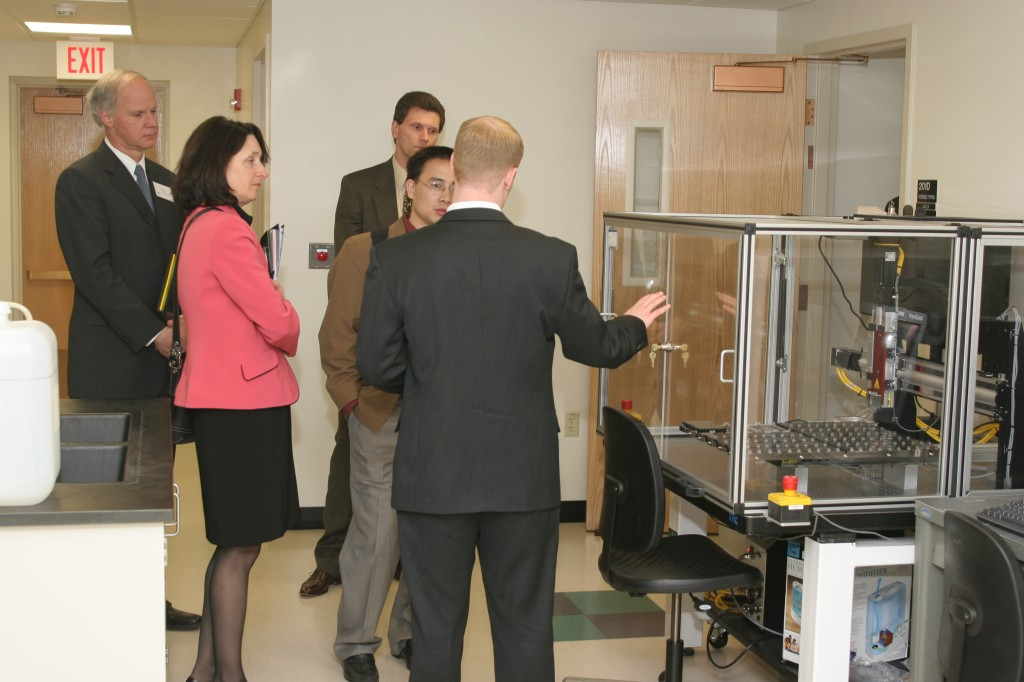 Graduate student, Joshua Suhl, leads a tour of the CAGT, explaining the Affymetrix Gene Machine chip printing robot.